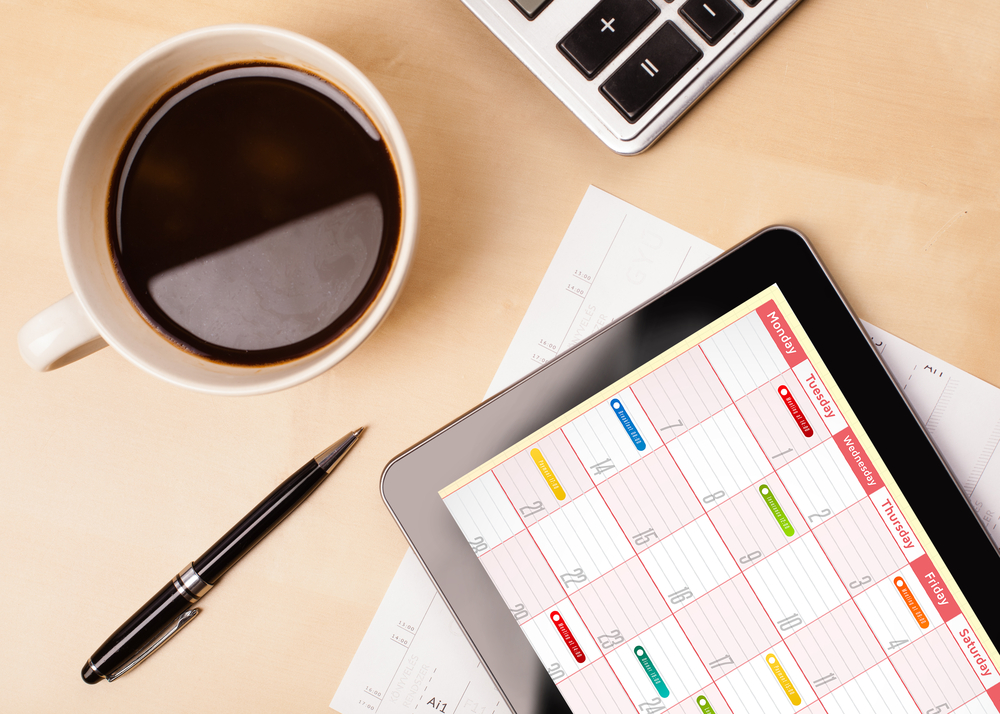 Tablet showing calendar alongside coffee and pen